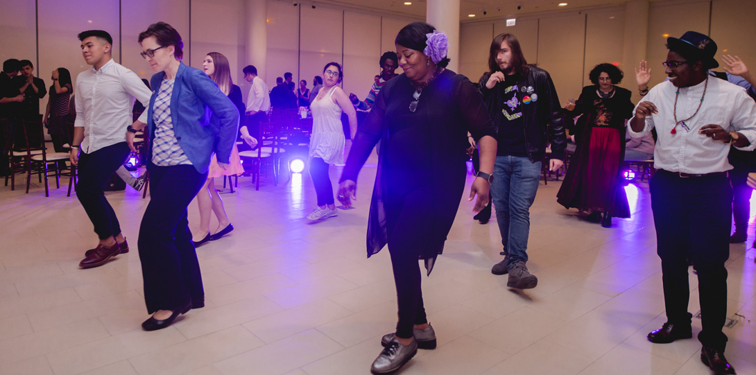 Guests doing a line dance with purple lighting reflecting on the floor.