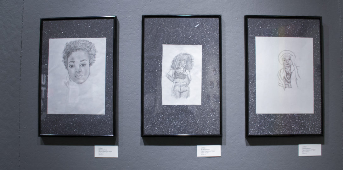 Photograph of three framed drawings (in pencil on white paper) on the grey space of the first wall.