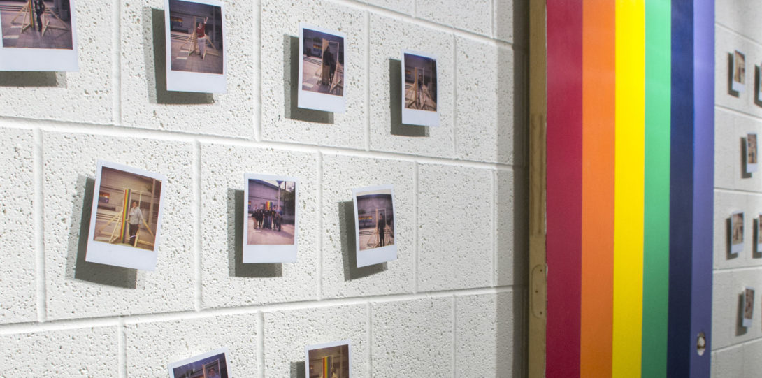 Photograph of part of the second wall of the exhibition. Here we can see small Polaroid photos on the wall surrounding a hanging door painted in rainbow. The Polaroids are old, and faded, with strange color shadings.