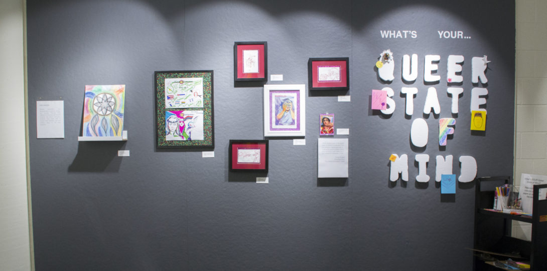 Photograph of the third wall, all grey space. There is (left to right) a piece on a ledge, a hanging piece with two drawings placed below one another, five framed images, four of similar size, and the writing