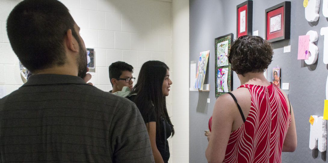 Photograph of multiple viewers looking at the third wall. Each stacked throughout the frame.
