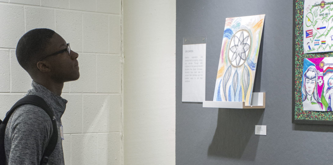 Photograph of a viewer looking at the third wall of the exhibition, another grey space on a white wall. Here they are looking at a piece on a ledge next to a piece hanging up (with two images). Viewer is looking at a drawing of a dream catcher.