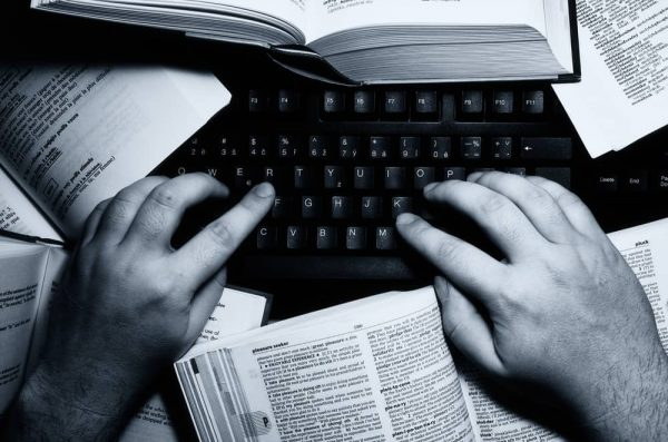 Black and white image of a person's hands while typing on a laptop surrounded by books.