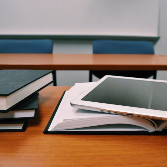 books and a tablet on a desk in a classroom