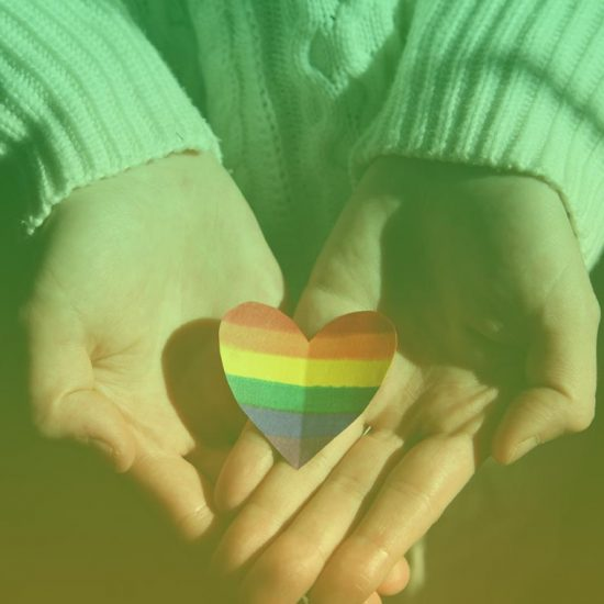a paper heart with the lgbt flag rainbow stripes on it is creased down the middle, and resting in the hands of a person with light skin and a white sweater.