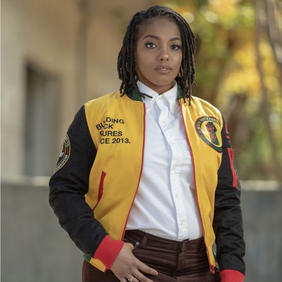 Janaé is in a yellow Jersey with black sleeves, a white button up shirt with a collar, and Maroon pants.